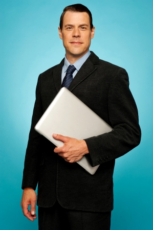 Businessperson carrying a laptop posing against blue background photo