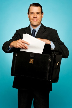 Male executive arranging paper works and keeping them safely in bag photo