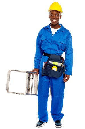 African repairman holding stepladder with tool bag around his waist isolated against white background photo