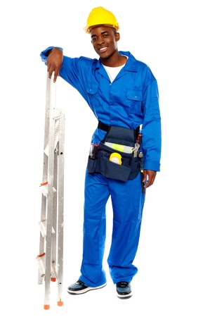 Full length portrait of smiling african worker resting hand on stepladder photo
