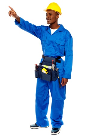 Young african male worker pointing at copy space, full length portrait photo