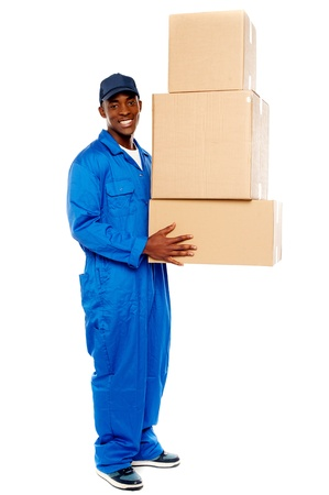 Smiling young delivery boy holding cardboard boxes isolated on white background photo