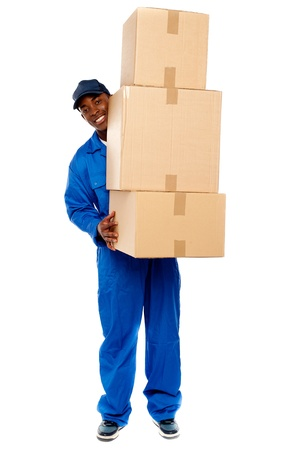Full length portrait of a delivery boy carrying heavy boxes isolated on white photo