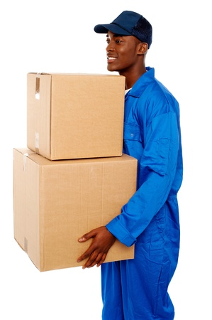 Young courier boy moving boxes looking away. Great services photo