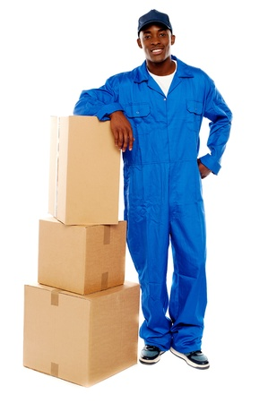 Courier boy standing beside boxes against white background, resting hand on them photo
