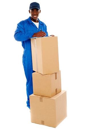 Cheerful delivery guy preparing receiving notice. Isolated over white photo