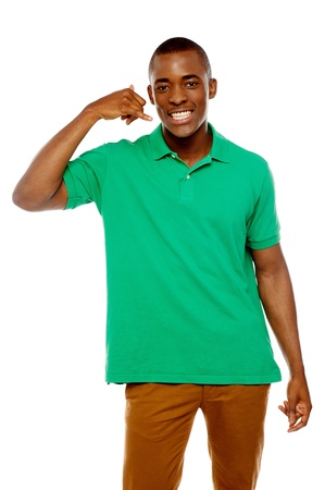 Happy young man with calling gesture over white background photo