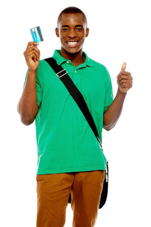 african student: Sorridente studente africano che mostra la carta di credito alla telecamera e con il pollice fino gesto