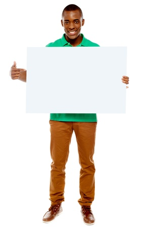Full length portrait of casual young guy pointing towards placard photo