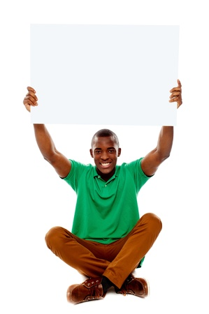 Seated young man holding white blank banner over his head photo