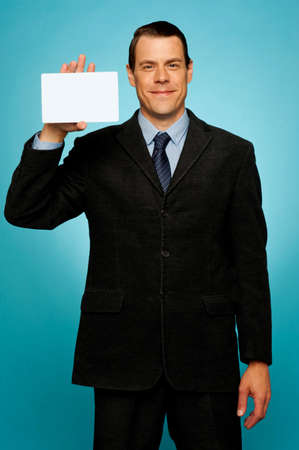 Isolated corporate man holding blank placard, showing it to camera photo