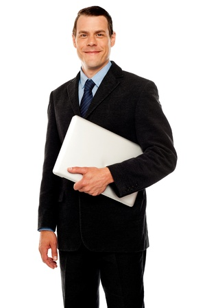 Handsome business executive holding laptop isolated against white background Stock Photo - 14603213
