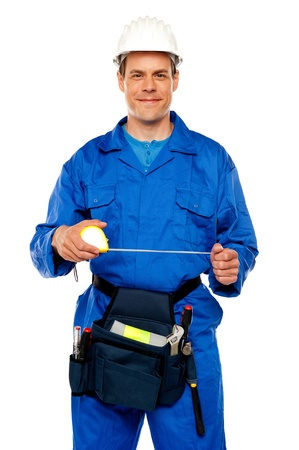 Male worker stretching measuring tape isolated against white background photo