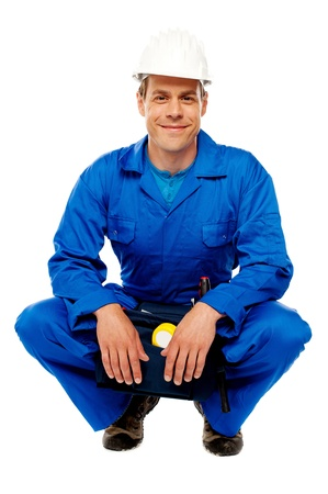 Smiling male worker wearing safety hat and relaxing, break from work photo