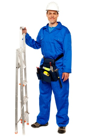 Repairman with a stepladder and tools bag standing against white background photo