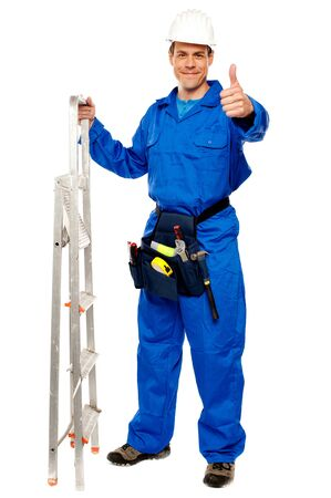 Repairman holding ladder and showing thumbs up gesture isolated on white photo