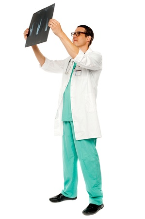 Experienced surgeon looking at patients x-ray,full length portrait photo