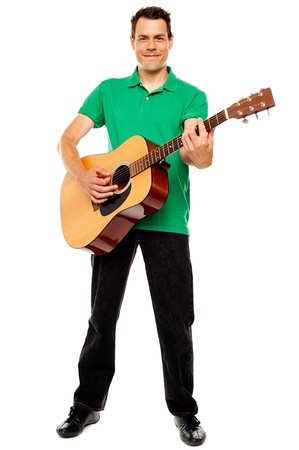 acoustic: Young caucasian guitarist playing tracks isolated over white background Stock Photo
