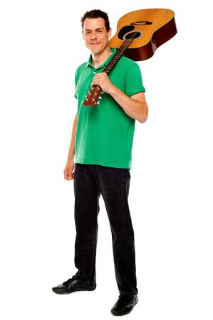 Casual music lover carrying guitar on his shoulders, full length portrait photo