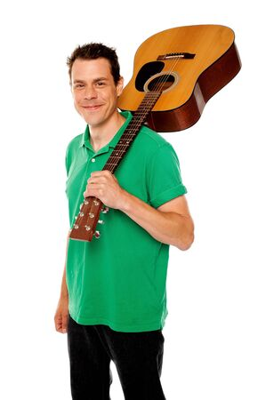 Cheerful handsome casual man with guitar on shoulders looking at camera photo