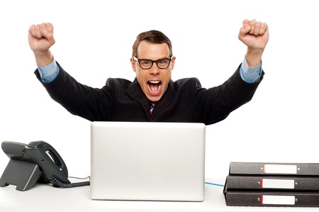 rejoicing: Excited businessman shouting and rejoicing his victory. Wearing glasses and arms raised up
