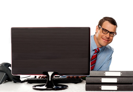 Man peeping from behind computer screen and enjoying at work. Sitting in office photo