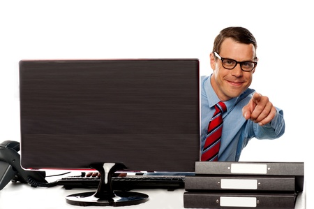 Male executive in glasses pointing at camera sitting in front of computer screen Stock Photo - 14603231