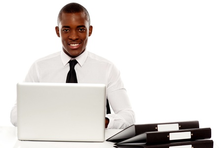 African corporate male manager at work desk using laptop and looking at camera Stock Photo - 14602680