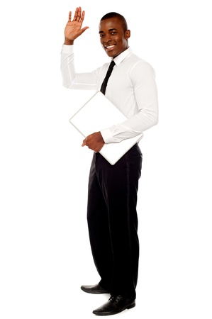 Full length portrait of handsome african businessman waving hand and holding laptop photo