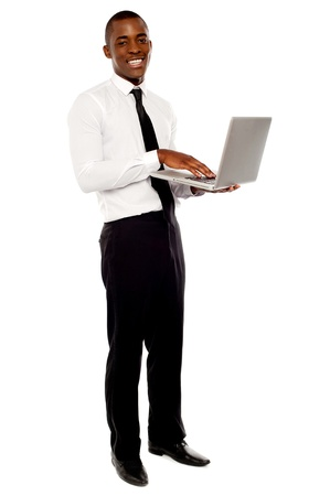 Full length portrait of businessperson holding laptop and using photo