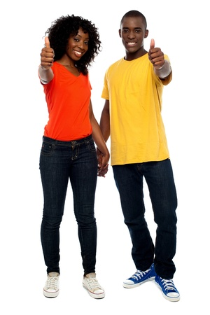 Full length portrait of happy african couple showing thumbs up photo
