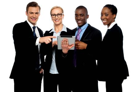 Business people pointing towards wireless tablet and smiling at camera Stock Photo - 14657436