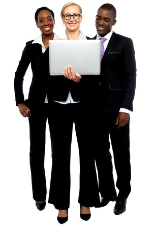 Group of business people looking into laptop. Full length portrait photo
