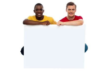 Casual young guys posing with blank billboard isolated against white background photo