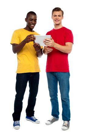 Full length shot of guys operating portable device against white background photo