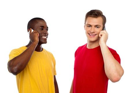 hablando por celular: Dos hombres guapos que se comunican por teléfono móvil. Chico africano mirando varones de raza caucásica. Foto de archivo