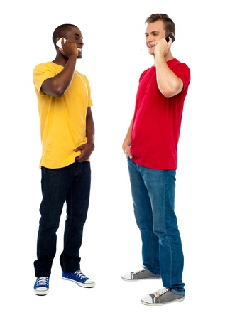 two men talking: Trendy handsome guys attending call on cellphone. Full length portrait