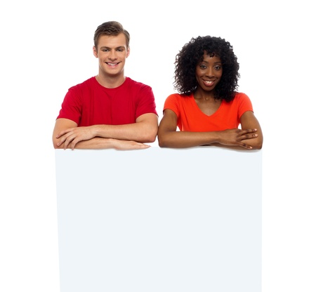Smiling young couple standing behind white billboard looking at camera photo