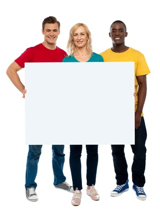 Caucasian young woman showing white adverting board while two guys standing beside her photo