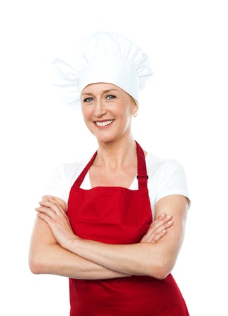 Middle aged female chef posing with crossed arms isolated against white background photo