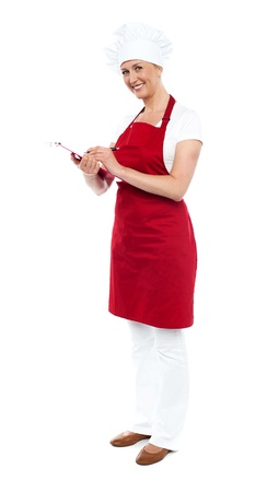 Full length shot of pretty smiling female cook writing recipe on notepad photo
