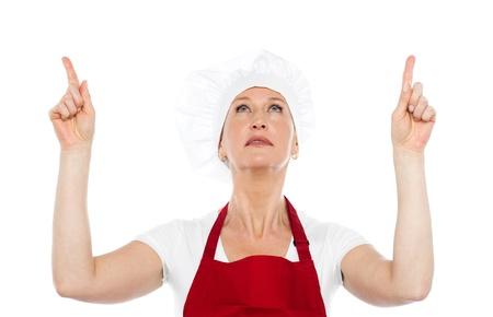 Isolated female chef in uniform pointing upwards against white background photo