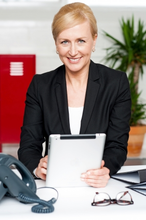 Cheerful businesswoman holding tablet pc and looking at camera Stock Photo - 14724719