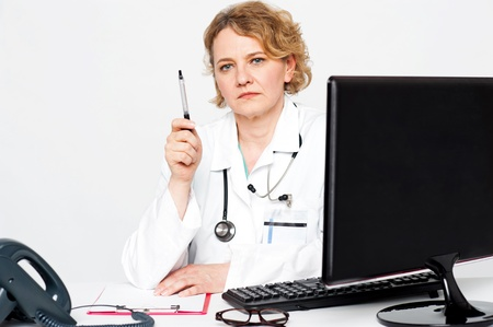 Serious aged doctor posing with pen in hand, showing it to camera photo