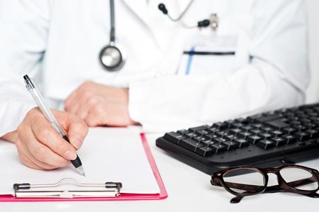 Closeup shot of female doctor writing prescription on notepad Stock Photo - 14736289