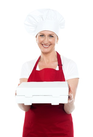 Female baker presenting pizza to you in a packed box. Enjoy your meal photo