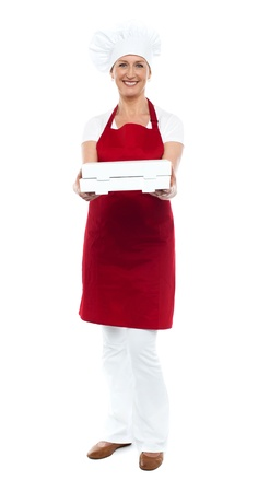 Full length portrait of woman chef offering hot fresh pizza packed well photo