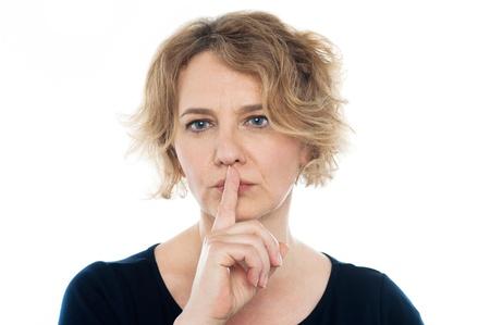 Woman gesturing silence at camera, closeup shot photo