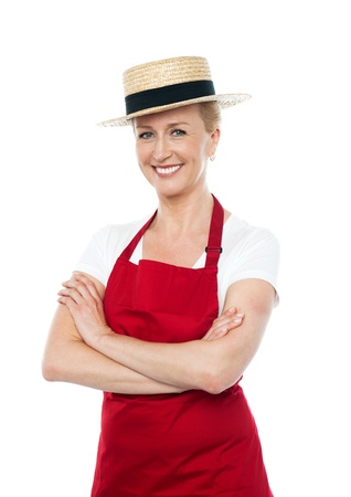 Confident cheerful female cook wearing hat and dressed in white and red uniform photo
