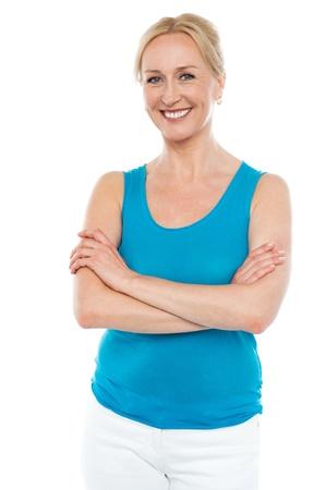 one senior adult woman: Hermosa mujer sonriente de pie con los brazos cruzados aislados sobre fondo blanco